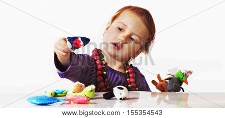 little cute girl playing indoors with colored animals (developmental toys for children)