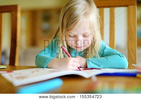 Cute Little Girl Is Drawing With Colorful Markers