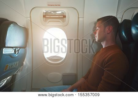 Comfortable traveling by airplane. Young passenger sleeping on the seat near the emergency exit from the aircraft.