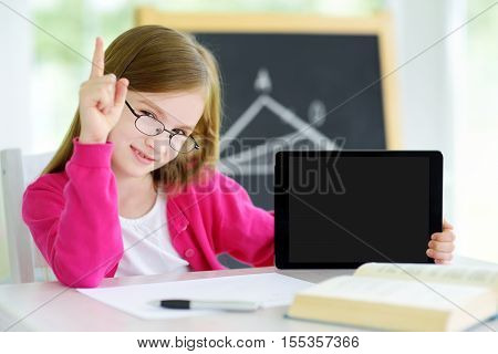 Smart Little Schoolgirl With Digital Tablet In A Classroom