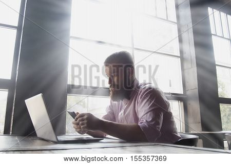 fashionable brutal bearded man working with laptip .handsome hipster man with beard