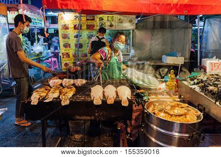 CHIANG MAI THAILAND - AUGUST 27: Thai woman cooks grilled fish at the Saturday Night Market on August 27 2016 in Chiang Mai Thailand.