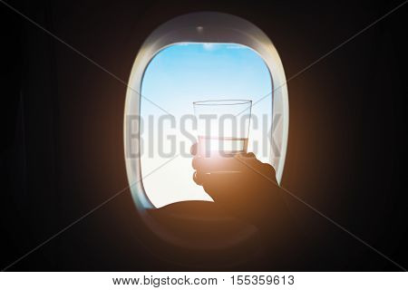 Comfortable traveling by airplane. Passenger is holding glass of the wine during the flight.
