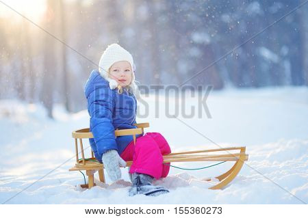 Funny Little Girl Having Fun With A Sleight In Winter Park