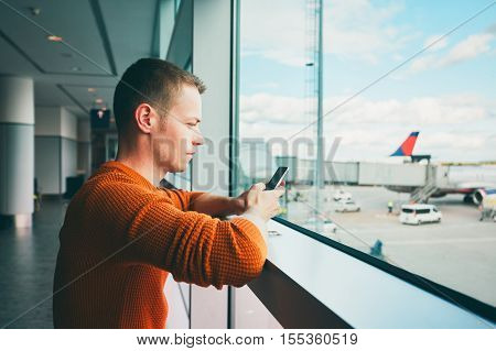 Young man with mobile phone waiting for a delayed flight inside airport terminal.