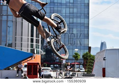 BMX sport jumping at a city background. Biking as extreme and fun sport.