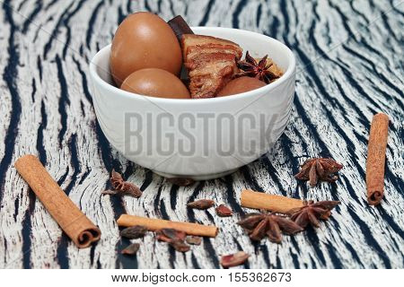 Thai Recipes : Stewed boiled egg with tofu and streaky pork call Khai Palo in Thai take photo with herbs as Chinese star anise cinnamonblack peppercilantro roots and stems is popular Thai food served. Selective focus.