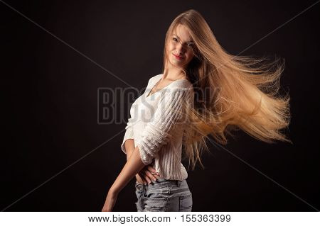 attractive teenager girl with flying hair isolated on black background
