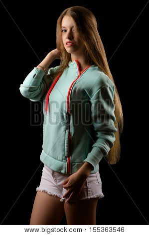 blond teenager girl in fashion windbreaker isolated on black background