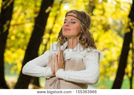 Beautiful boho girl enjoys meditating in the park.
