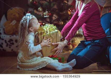 Mother and daughter exchanging Christmas gifts near tree