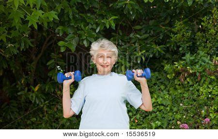 Reife Frau ihre Übungen im Garten