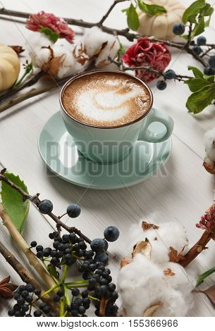 Pumpkin spice latte. Blue coffee cup with creamy foam, autumn dried flowers, sloe and small yellow pumpkins at white wood background. Fall hot drinks, seasonal offer concept