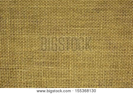 Densely woven material made of string with clearly visible strands and fine threads in light brazowym.Texture and background. Close horizontal view