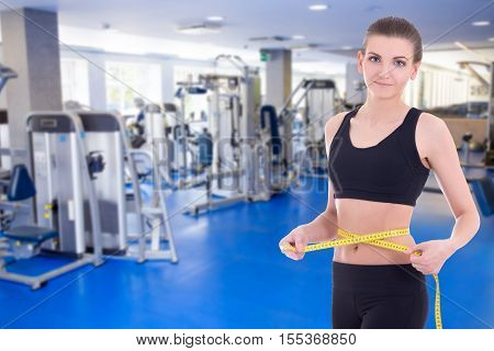 sport concept - beautiful slim sporty woman measuring her waistline with measure tape in modern gym