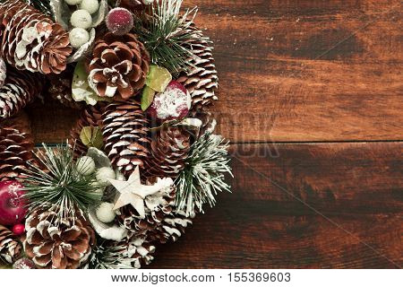 Delicate Christmas wreath of pine cones on wooden background
