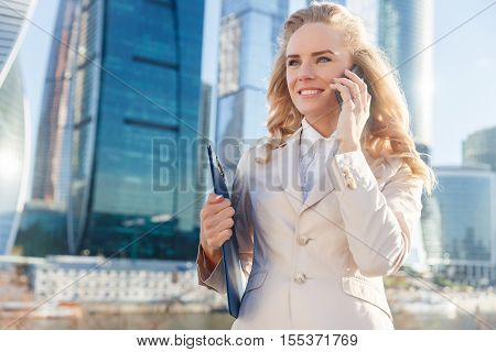 Portrait of young beautiful business woman talking on mobile phone and holding folder on the street near the modern office building on sunny autumn day