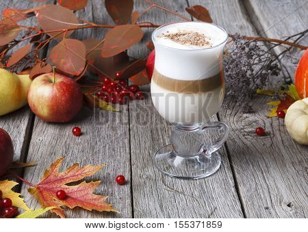 Pumpkin spice latte background. Glass coffee cup with creamy foam, autumn dried leaves, apples and small yellow pumpkin cubes at rustic wood. Fall hot drinks, seasonal offer concept