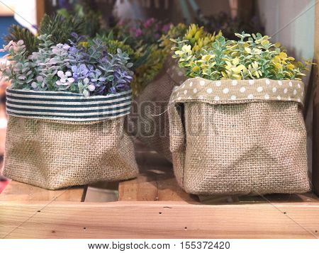 Artificial flowers in flowerpots on shelf for interior decoration.