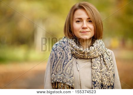 Portrait of cute smiling caucasian woman in warm autumn coat and fancy tippet on blurred natural background