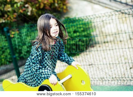 happy cute little girl in playground outdoors