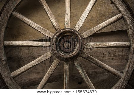 Old wooden wheel used for transportation on a wooden wall.