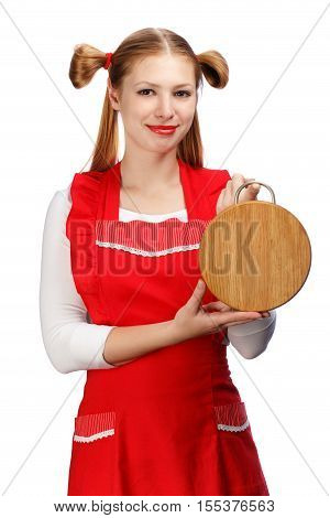 Young beautiful smiling housewife in bright red apron with funny ponytails holding wooden cutting board isolated on white background.