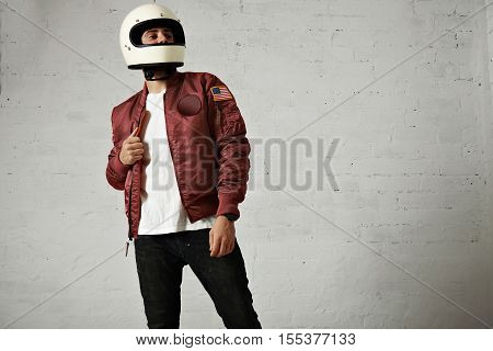 Proud looking motorbiker in a plain white helmet, bordeaux nylon bomber jacket, jeans and t-shirt against white wall background