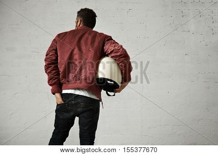 A man in military bomber jacket with a motorcycle helmet under his arm reaches into the back pocket of his skinny black jeans, back shot