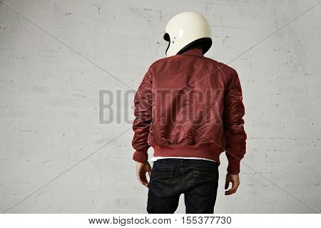 Back shot of a motorcyclist in white helmet and burgundy bomber jacket isolated on white