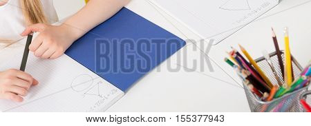 Child doing homework and drawing geometric figures in notebook