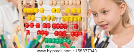 Close-up of children using abacus during math lesson