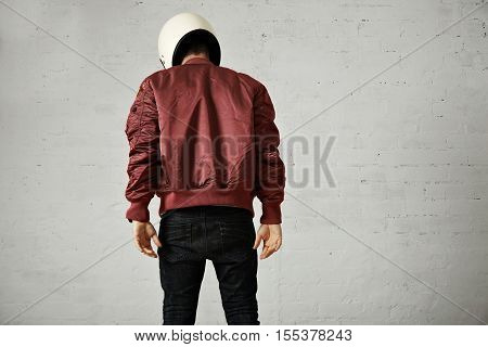 Athletic young model in skinny jeans, terracotta bomber jacket and white motorcycle helmet isolated on white, back shot