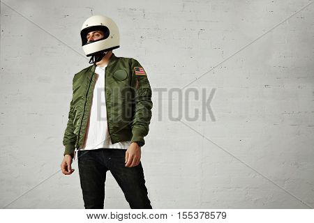 Young attractive male model in black jeans, plain white t-shirt, green bomber jacket and a white motorcycle helmet