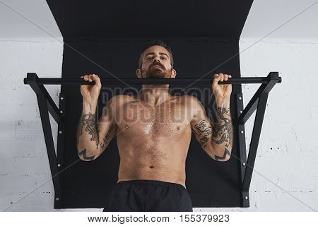 Strong tattooed topless male athlete shows calisthenic moves close up of classic pullup hold in top bar