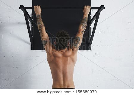 Back view on muscular topless male athlete showing calisthenic moves Hanging on pullbar