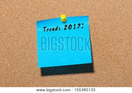 Trends 2017 written at blue sticker pinned at notice board. New year business and fashion innovation.