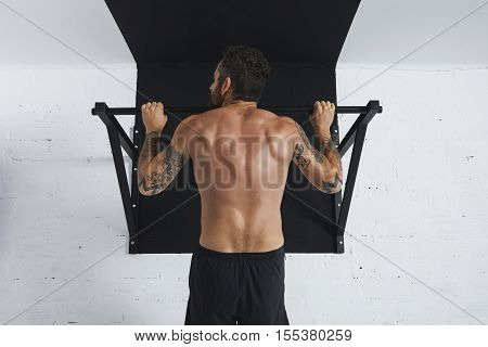 Back view on muscular topless male athlete showing calisthenic moves Pull up on pullbar, head looking on left side direction