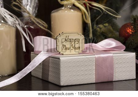 happy new year white gift box with a pink ribbon tied in a bow candles Christmas decorations