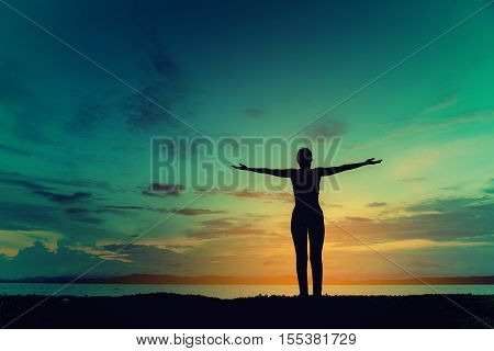 Silhouette happy woman on the beach at sunset. Vintage tone