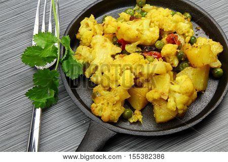 A skillet with cauliflower bhaji on a stone grey background.