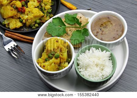 A vegetarian platter with cauliflower curry brown lentils with rice and chapati