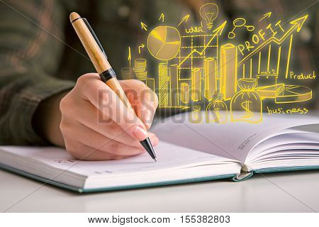Close up of hand writing in notepad with abstract financial sketch. Business planning concept