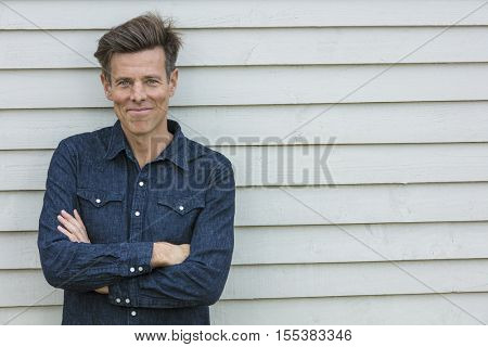 Portrait shot of an attractive, successful and happy middle aged man male arms folded outside wearing a blue denim shirt