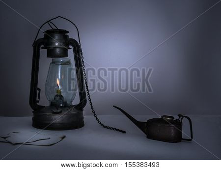 kerosene lamp, oiler, a notebook on a table in the twilight