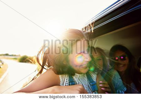 Laughing vivacious teenager travelling with friends in a car backlit with the rising summer sun as she leans out of a window to enjoy the breeze