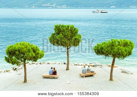 Two couples of different ages sitting on the beach of Limone sul Garda Italy.
