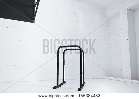 Calisthenics parallel bars isolated in empty white room next to black pull bar