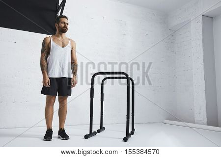 Brutal tattooed bearded male athlete in blank white tank t-shirt standing near to parallel bars and pull bar looking on side , ready to workout