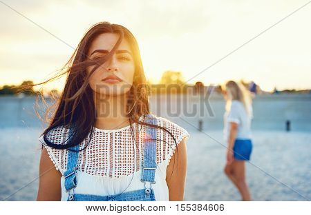 Wind blowing through hair of beautiful young adult woman in white blouse and blue jeans overalls. Sunlight in background.
